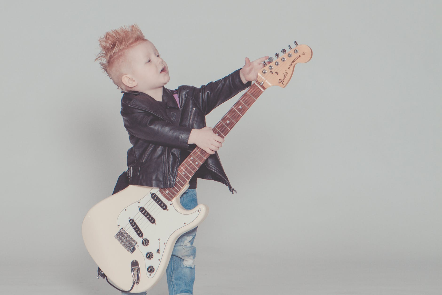 boy wearing black jacket holding electric guitar