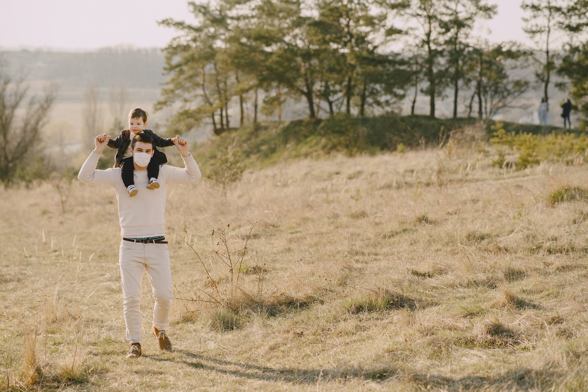 photo of man carrying his child on his back while standing on grass field